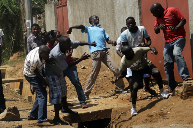 Protester throw stones at police during clashes in the Nyakabyga neighborhood of Bujumbura, Burundi, Thursday May 21, 2015. (Photo by Jerome Delay/AP Photo)