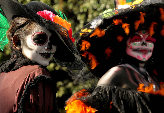 People take part in the Day of the Dead parade in Mexico City on October 27, 2018. (Photo by Ulises Ruiz/AFP Photo)