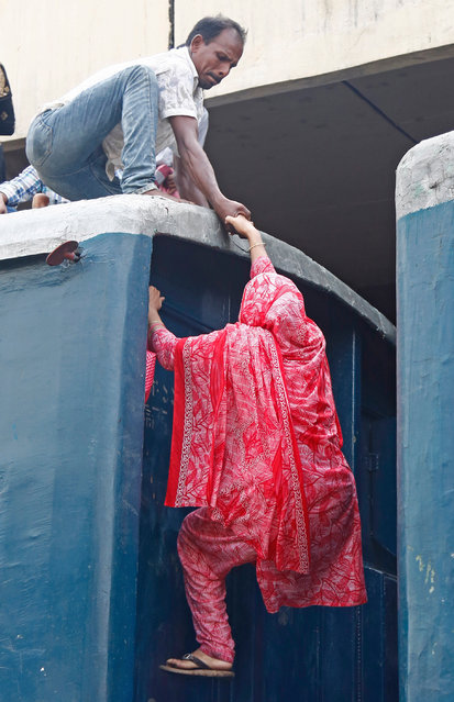 Bangladeshi people climb into the roof of an overcrowded train as they travel to celebrate Eid with family in their villages, at the Kamlapur Railway Station in Dhaka, Bangladesh, 03 June 2019. Muslims around the world are preparing to celebrate Eid al-Fitr, the three-day festival marking the end of the Muslim holy month of Ramadan, Eid al-Fitr is one of the two major holidays in Islam. (Photo by Monirul Alam/EPA/EFE)
