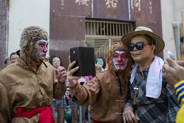 A man playing the role of the Monkey King takes a selfie with his colleague during a Bun Festival parade at Hong Kong's Cheung Chau island, China May 25, 2015. (Photo by Tyrone Siu/Reuters)