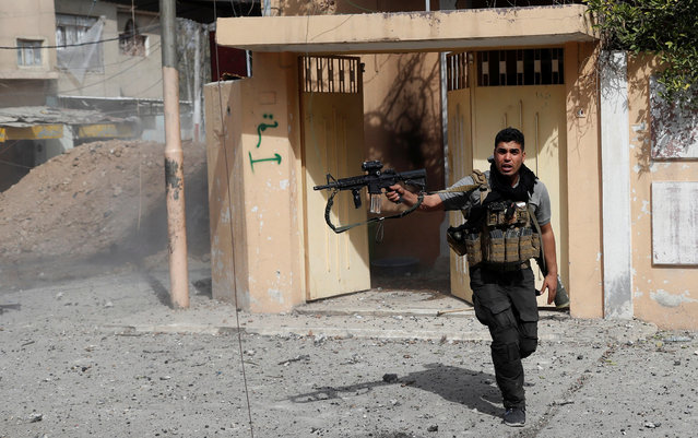 An Iraqi special forces soldier runs for cover as he fires his rifle during a battle with Islamic State militants in Mosul, Iraq March 1, 2017. (Photo by Goran Tomasevic/Reuters)