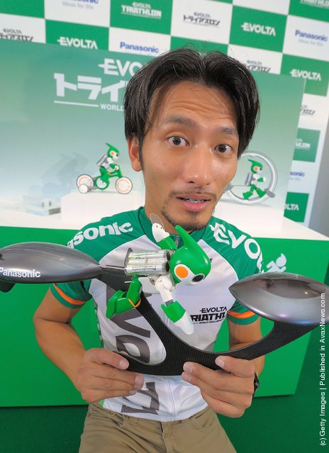 Robot creator Tomotaka Takahashi poses with the swim version of his 'Evolta' robot