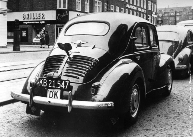 1964: The back view of a Renault 4 CV car, parked in the centre of Copenhagen with a large key fitted to the boot giving passers-by the impression of a life-size clockwork car