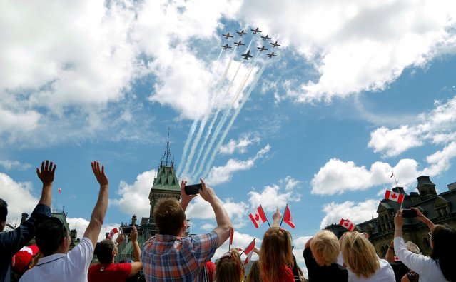 Canadians wave as the Snowbirds aerobatics team fly past during Canada Day festivities on Parliament Hill in Ottawa, Ontario, Canada on July 1, 2019. (Photo by Patrick Doyle/Reuters)