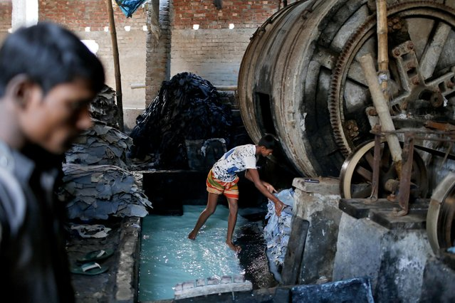 In this Monday, February 6, 2017 photo, a Bangladeshi boy processes animal hide inside a factory at the highly polluted Hazaribagh tannery area in Dhaka, Bangladesh. (Photo by A.M. Ahad/AP Photo)