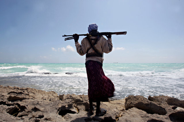 A file picture taken on January 7, 2010 shows an armed Somali pirate along the coastline while the Greek cargo ship, MV Filitsa, is seen anchored just off the shores of Hobyo town in northeastern Somalia where its being held by pirates. Attacks on the world's seas are soaring as armed and dangerous pirates become increasingly emboldened, seizing more ships than before and taking even bigger risks, an international body said on July 14, 2011. (Photo by Mohamed Dahir/AFP Photo)