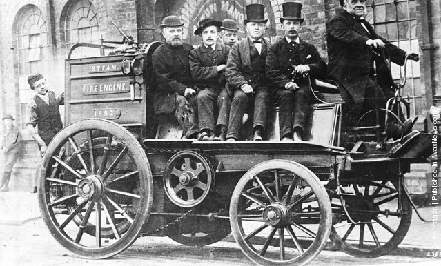 1879: A steam driven Victorian fire engine with 'crew' aboard