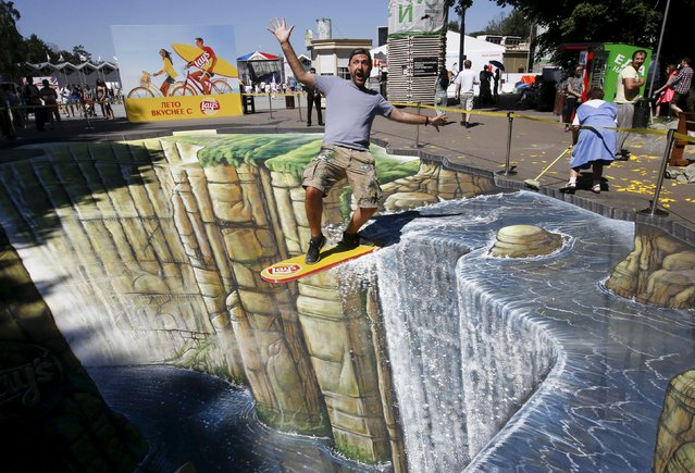 "Artist Joe Hill poses on his 3D artwork, from the ""Joe and Max"" project as part of an advertising campaign, during its presentation at a park in Moscow, Russia, July 4, 2015. (Photo by Sergei Karpukhin/Reuters)"