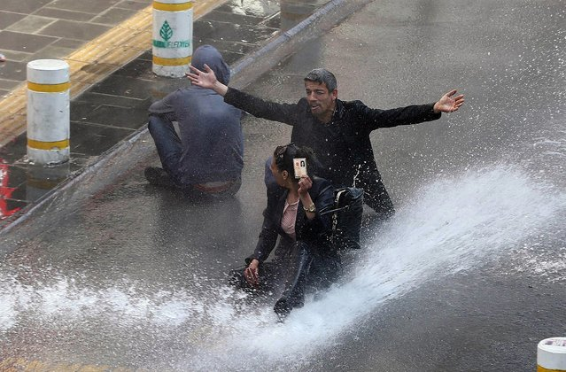 A woman shows her identity card next to another protestor as riot police uses water cannons during clashes after hundreds of people tried to reach the city's main Kizilay Square to celebrate May Day in Ankara on May 1, 2014. Earlier, riot police in Istanbul used water cannon and tear gas against thousands of protesters who tried to defy a May Day ban on demonstrations, injuring at least 50 people. (Photo by Adem Altan/AFP Photo)