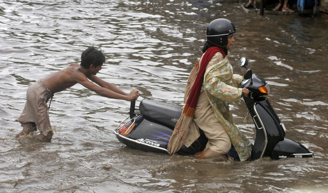 A boy helps a woman on a scooter to cross a flooded road after heavy rain in Ahmedabad July 11, 2008. (Photo by Amit Dave/Reuters)