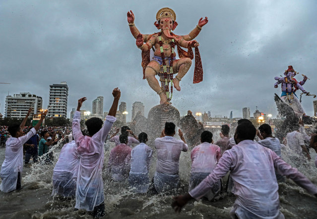 Indian devotees carry idols of elephant-headed Hindu god Lord Ganesha for immersion into the Arabian Sea, as part of a ritual of the Ganpati festival in Mumbai, India, 12 September 2019. The Ganesh festival comes to an end on the day of Anant Chaturdashi. During the Ganpati festival, that is celebrated as the birthday of Lord Ganesha, idols of the Hindu deity are worshipped at hundreds of pandals or makeshift tents before they are immersed into water. (Photo by Divyakant Solanki/EPA/EFE)