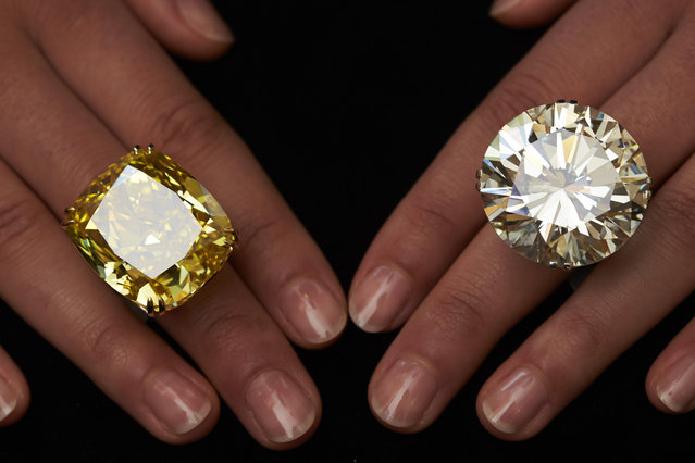 A model poses with a vivid yellow 100.09 carats diamond (L) and a 103.46 carats diamond ring during an auction preview at Sotheby's in Geneva May 7, 2014. These items are expected to reach between CHF 13,250,000 to 22,250,000 (USD 15,000,000 to 25,000,000) and CHF 3,100,00 and 4,450,000 (USD 3,500,00 to 5,000,000) when they go on sale May 13, 2014 in Geneva. (Photo by Denis Balibouse/Reuters)