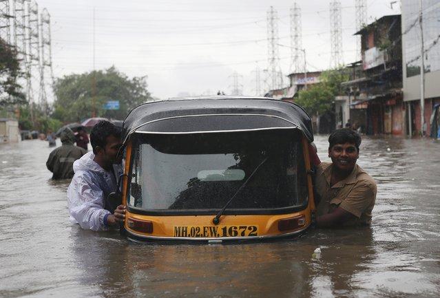Men push an auto-rickshaw through a flooded road after a heavy rainfall in Mumbai, September 4, 2019. (Photo by Francis Mascarenhas/Reuters)