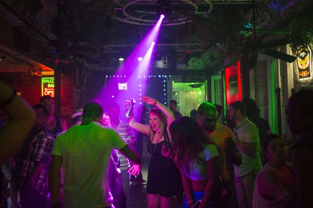 Revelers dance in a club along Bourbon Street, located in the French Quarter of New Orleans, Louisiana, July 11, 2015. (Photo by Adrees Latif/Reuters)