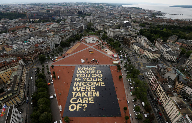"A 8,000 square meter poster is pictured on the Plainpalais square in Geneva, Switzerland May 14, 2016. The committee for the initiative for an ""Unconditional Basic Income"" has crowdfunded the ""world's biggest poster"", posing the question ""What would you do if your income were taken care of?"". Swiss citizens will vote on June 5, 2016 on the proposal for an ""Unconditional Basic Income"". (Photo by Denis Balibouse/Reuters)"