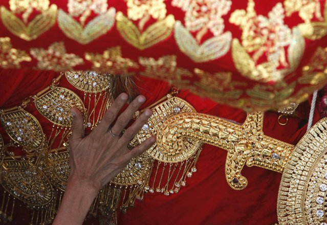 A hand of a Shi'ite Muslim woman reaches out to touch the gold-ornamentation of sword and shield, placed on a symbolic sacred horse for a good luck, during the religious procession of Yaum-e-Ali, marking the death anniversary of Imam Ali Ibn Abu Talib, son-in-law of Prophet Mohammad, in Karachi, Pakistan July 9, 2015. Imam Ali, who was also the cousin of Prophet Mohammad, died in 661 AD in Najaf. (Photo by Akhtar Soomro/Reuters)