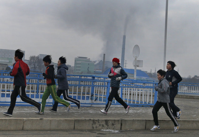 In this December 15, 2018, photo, young joggers pass by as smokes billows from the stack of the Pyongyang Power Plant in Pyongyang, North Korea. North Korea is exploring two ambitious alternative energy sources, tidal power and the production of coal-based synthetic fuels, that could greatly improve its standard of living while reducing its reliance on oil imports and vulnerability to sanctions. (Photo by Dita Alangkara/AP Photo)