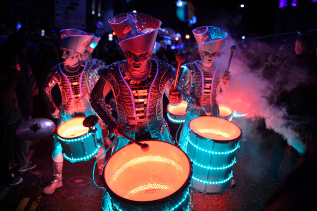 "Performers with ""Spark!"", an LED-illuminated theatrical drumming ensemble, entertain the public during the annual ""Light Night Leeds"" festival of visual arts in the centre of Leeds, northern England on October 10, 2019. Celebrating the diverse and thriving creativity of Leeds, Light Night Leeds is an annual free multi-arts and light festival that takes over Leeds City Centre for two nights in October. (Photo by Oli Scarff/AFP Photo)"