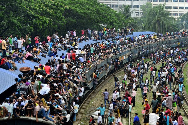 Bangladeshi travellers cram onto a train as they try to get home to their respective villages to be with their families ahead of the Muslim festival of Eid al-Fitr in Dhaka on July 16 , 2015. Eid al-Fitr is the largest festive event in the Muslim calendar and marks the end of the month of Ramadan. (Photo by Munir Uz Zaman/AFP Photo)