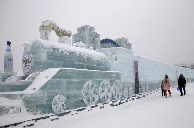 Visitors walk past a train-shaped ice sculpture ahead of the 31st Harbin International Ice and Snow Festival in the northern city of Harbin, Heilongjiang province, in this January 4, 2015 file photo. (Photo by Kim Kyung-Hoon/Reuters)