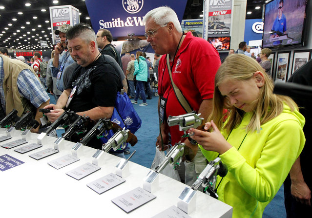 Kelsey Bartley (10) looks over Smith & Wesson guns with her dad Rick Bartley at the National Rifle Association's annual meetings & exhibits show in Louisville, Kentucky, May 21, 2016. (Photo by John Sommers II/Reuters)