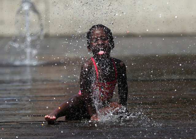 A girl plays with water in a fountain during a hot summer day in Brussels, Belgium, July 24, 2019. (Photo by Yves Herman/Reuters)