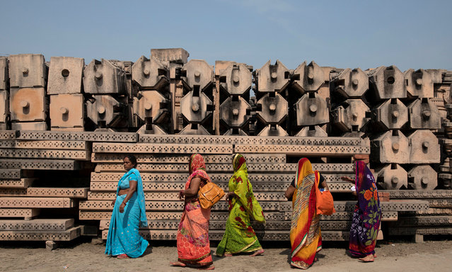 Devotees walk past the pillars that Hindu nationalist group Vishva Hindu Parishad (VHP) say will be used to build a Ram temple at the disputed religious site in Ayodhya, India, October 22, 2019. (Photo by Danish Siddiqui/Reuters)