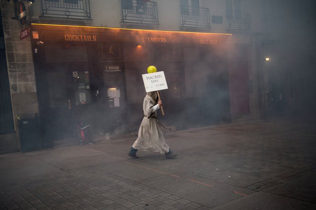 "A man wearing a monk suit holds a placard reading ""Macron get out this body"" as he walks on November 16, 2019, in Nantes, western France during clashes on the sidelines of a demonstration marking the first anniversary of the ""yellow vest"" (gilets jaunes) movement. French ""yellow vest"" protesters are planning a series of nationwide demonstrations this weekend in a bid to show the government they can still muster support on the first anniversary of their movement. Numbers attending the protests and levels of violence have sharply diminished in recent months from the height of the movement, which began on November 17 last year with a giant Paris protest that drew almost 300,000 people. (Photo by Loic Venance/AFP Photo)"