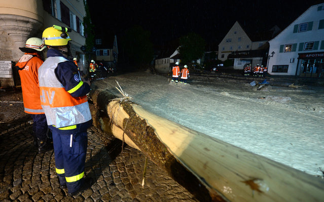 Firefighters work at a flooded street in Braunsbach, southwestern Germany, Monday, May 30, 2016. (Photo by Franziska Kraufmann/DPA via AP Photo)
