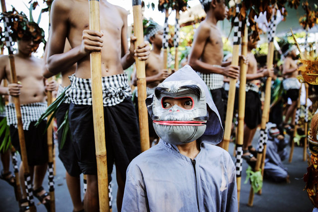 A boy wearing monkey costum and mask stands as after his art performace during the opening of the 36th Bali International Arts Festival on June 13, 2014 in Denpasar, Bali, Indonesia. The annual month-long festival runs from June 13 to July 12, 2014 and features 12.000 local and international art performers. (Photo by Agung Parameswara/Getty Images)
