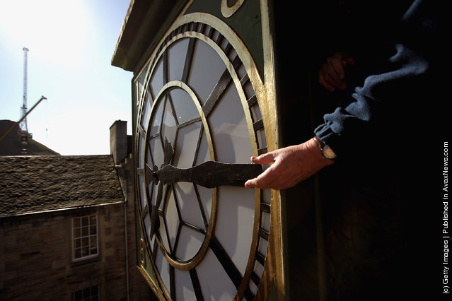 Alan Wilson, Director of James Ritchie & Son clockmakers, founded in 1809, adjusts a clock face at the Cannongate Tobooth to British Summer Time in Edinburgh