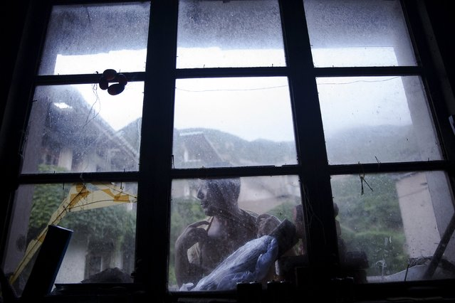 Sun Ayue, one of very few residents of the abandoned fishing village of Houtouwan on the island of Shengshan is seen from inside the room where he lives July 25, 2015. Sun, a 59-year-old former fisherman who doesn't often leave the village, except for an occasional game of mahjong in the town across the hill, lives alone in a house with no running water and electricity. (Photo by Damir Sagolj/Reuters)