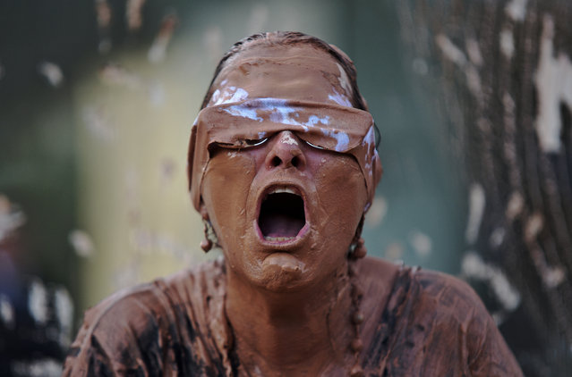 A protestor covered in mud performs during a demonstration in front of the headquarters of Brazilian mining company Vale in Rio de Janeiro, Brazil, on January 28, 2019. A tsunami of mineral-laced mud broke through a dam at an iron-ore mine owned by Vale near the town of Brumadinho on January 25 with the official toll of the disaster standing so far at 65 dead and around 280 missing. (Photo by Fabio Teixeira/AFP Photo)