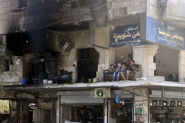 Residents sit on a couch on a balcony of a damaged building in Aleppo's al-Shaar neighboirhood, Syria, August 1, 2015. (Photo by Abdalrhman Ismail/Reuters)