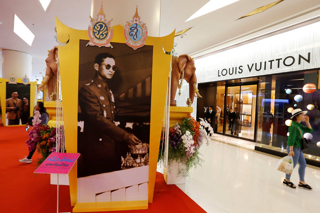"""People walk past a picture of Thailand's King Bhumibol Adulyadej during the """"Royal Orchid Paradise"""" exhibition inside a shopping mall in Bangkok, Thailand, June 7, 2016. (Photo by Jorge Silva/Reuters)"""