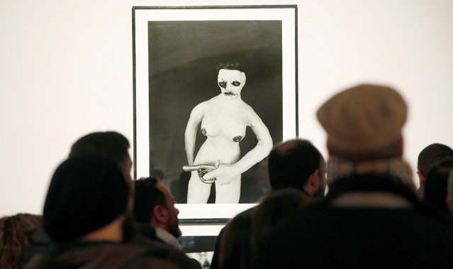 """Visitors stand in front of an artwork by US film director David Lynch as part of the exhibition """"Small Stories"""" at the Old Institute Cultural Center in Gijon, Asturias, northern Spain, 14 November 2019. """"Small Stories"""", which is on display as part of the Gijon International Film Festival cultural activities, frames 55 black and white pictures made by Lynch. The exhibition runs from 15 November 2019 to 26 January 2020. (Photo by Alberto Morante/EPA/EFE)"""