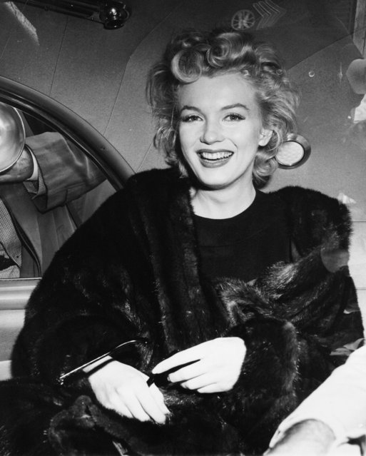 In this undated file photo, actress Marilyn Monroe smiles in a car after arriving from an all-night plane flight from Hollywood to Idlewild Airport, in New York. (Photo by AP Photo)