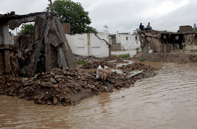 Local residents sit over the rubble of their demolished houses caused by heavy rains in a suburb of Peshawar, Pakistan, Sunday, July 26, 2015. (Photo by Muhammad Sajjad/AP Photo)