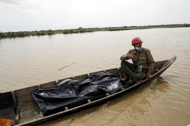 Rescue workers transport the body of a person who died in a storm, on a boat in Mrauk-U township, Rakhine state August 4, 2015. (Photo by Soe Zeya Tun/Reuters)