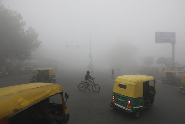 A cyclist pedals across a crossing amidst early morning dense fog in New Delhi, India, Monday, December 30, 2019. Delhi, which is witnessing the longest spell of cold weather in the last 22 years, woke up to a blanket of dense fog engulfing most parts of the national capital on Monday morning, disrupting rail, road and air traffic adversely. (Photo by Manish Swarup/AP Photo)