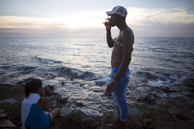 Street seller Joel Gonzalez, 29, (R) drinks as he watches the sunset with medical student Anaili Puig, 19, in Havana July 12, 2015. (Photo by Alexandre Meneghini/Reuters)