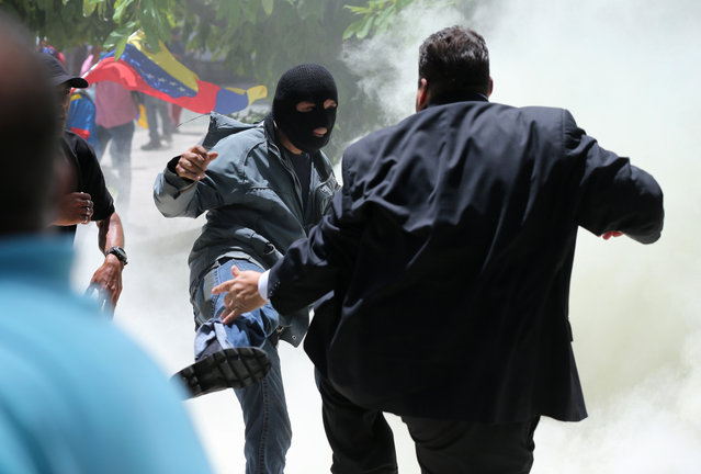A masked men kicks at opposition lawmaker Franco Casella in a melee with pro-government militias who tried to forced their way into the National Assembly during a special session coinciding with Venezuela's independence day, in Caracas, Wednesday, July 5, 2017. At least five lawmakers were injured in the attack. (Photo by Fernando Llano/AP Photo)
