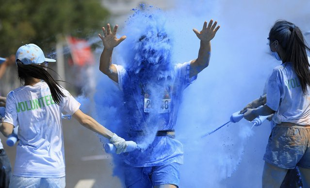 A participant (C) reacts as he is sprayed with coloured powder during a 5-kilometre Color Run in Shenyang, Liaoning province July 5, 2014. (Photo by Reuters/Stringer)