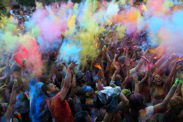 Revelers throw colored powders in the air during the Monsoon Holi Festival, in Madrid, Spain, Saturday, August 8, 2015. The festival, which is mainly celebrated during the Hindu spring festival Holi in some regions of India and Nepal, has become popular among people in other communities. (Photo by Francisco Seco/AP Photo)