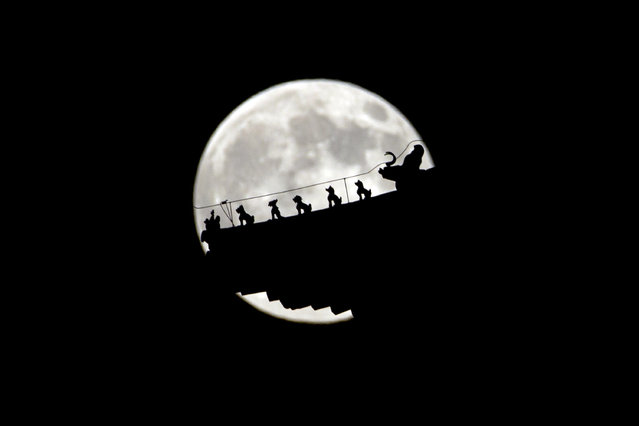 """A perigee moon also known as a supermoon rises behind figurines on a Chinese pavilion in Beijing, China, Saturday, July 12, 2014. The phenomenon, which scientists call a """"perigee moon"""", occurs when the moon is near the horizon and appears larger and brighter than other full moons. (Photo by Ng Han Guan/AP Photo)"""