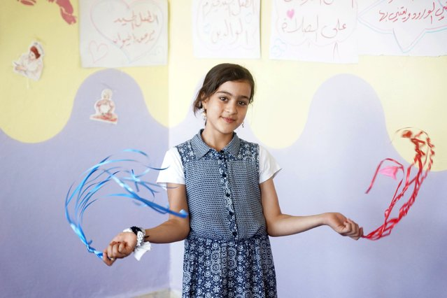 A girl dances during the opening of a psychological support centre for children in Da'el town, north of Deraa, Syria, August 1, 2015. (Photo by Alaa Al-Faqir/Reuters)