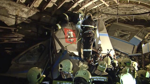 In this frame grab provided by the Russian Ministry for Emergency Situations shows frame grab from a video showing rescue teams working inside the tunnel where several cars of the wrecked train look almost coiled, occupying the entire space of the tunnel of Moscow subway in Moscow, Russia, on Tuesday, July 15, 2014. (Photo by AP Photo/Russian Emergency Situation Ministry)