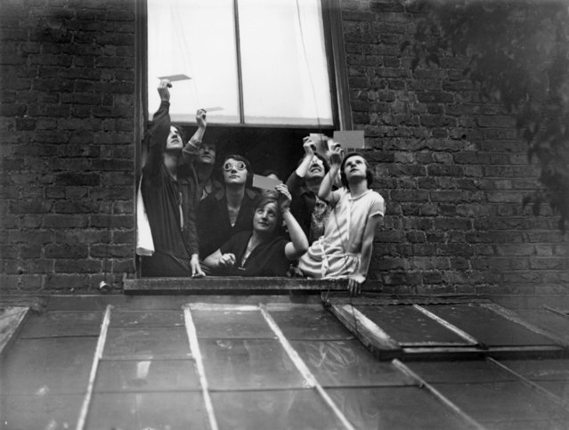 A group gathered in a window to view the total solar eclipse over London through smoked glass on June 29, 1927. (Photo by H. F. Davis/Topical Press Agency/Getty Images)