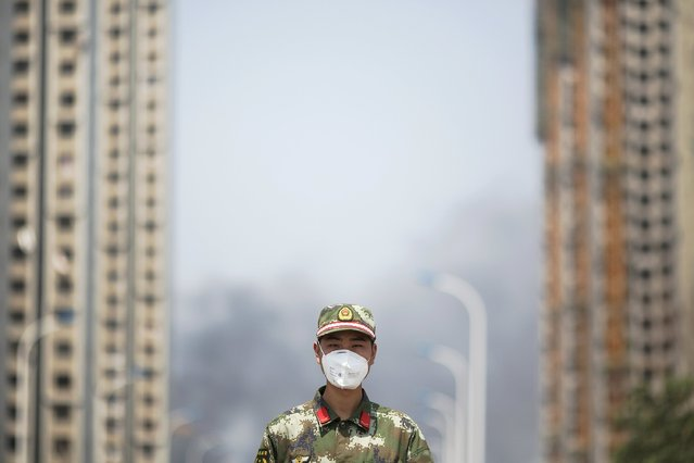 A paramilitary policeman wears a mask as he blocks the road leading to evacuated residential area and the explosion site in Binhai new district in Tianjin, China August 13, 2015. (Photo by Damir Sagolj/Reuters)