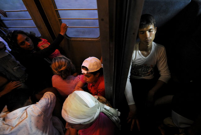 Migrants rest on a train as it travels through Macedonia August 2, 2015. (Photo by Ognen Teofilovski/Reuters)